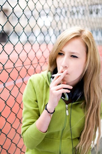 a teen girl smoking by a chain link fence