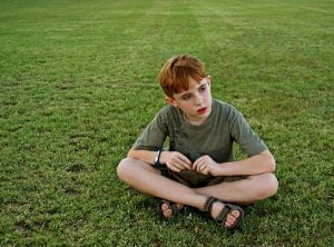 boy sits in field